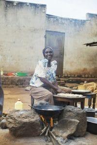 Frau bereitet Bananenpfannkuchen in Uganda zu